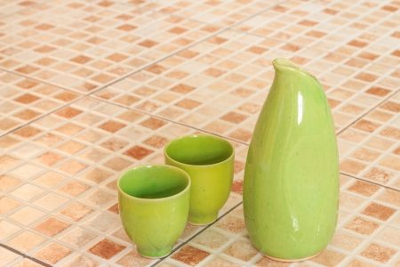 Image of light green Sake jug with 2 cups on orange glazed tile floor  photo