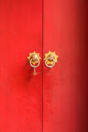 The China style door made from wood painted with red color, with the modern u type lock hanging on knob