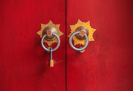 The Chinese style door made from wood painted with red color, with the modern u type lock hanging on knob due to required of secure
