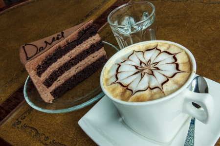 mocca: A cup of coffee Mocca served together with chocolate cake