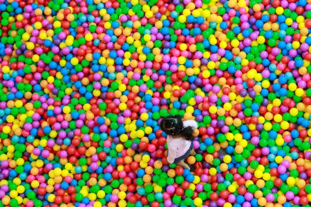 Girl walking at colorful plastic balls playground high view photo