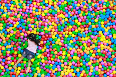 Girl playing at colorful plastic balls playground high view photo