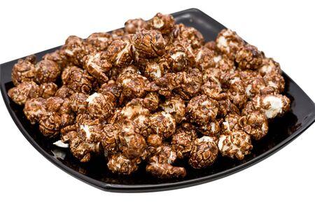 Schokolade Popcorn auf der schwarzen Platte isoliert auf wei�em