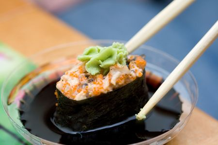 taking sushi with chicken and wasabi from plastic saucer with chopsticks