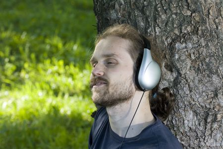 young man with mp3 pleer relaxing in the shadow Stock Photo