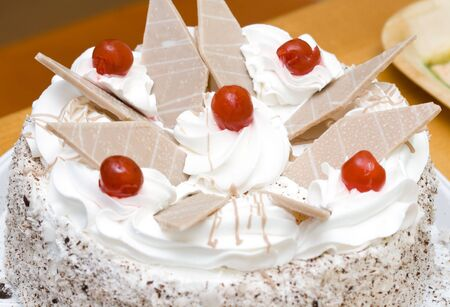 fresh cream cake with sugared cherry and chocolate pieces Stock Photo