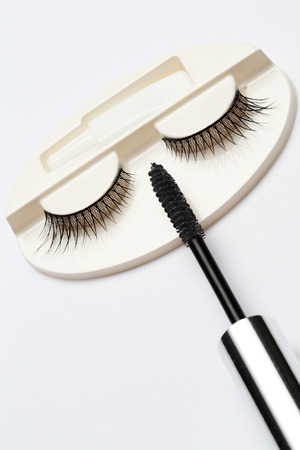 false eyelash set and mascara brush on grey background  photo