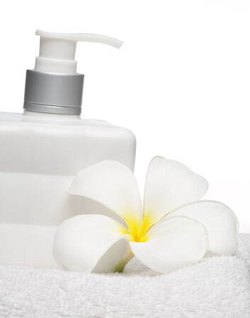 square bottle soap and flower on white towel white background  photo
