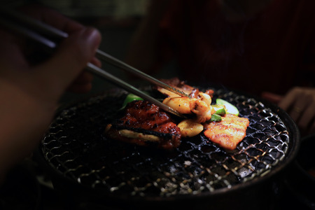 Barbecue meat on grilling mesh of charcoal fire. Korean or japanese traditional food grilling style barbecue. Stock Photo