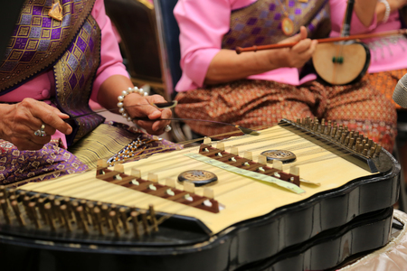 Women with thai national dress playing dulcimer in Thai traditional music show.