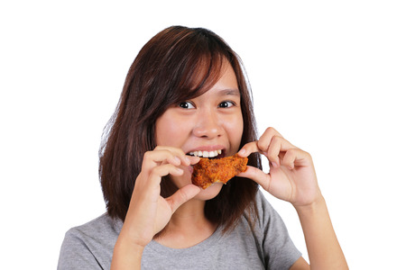 Young Asian woman eating chicken isolated on white background Stock Photo