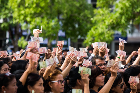 SURATTHANI, THAILAND - OCTOBER 16 : Crowds of mourners hold Thai cash for show picture of King Bhumibol during mourning ceremony at Suratthani City Hall on October 16, 2016 in Suratthani, Thailand. Editorial