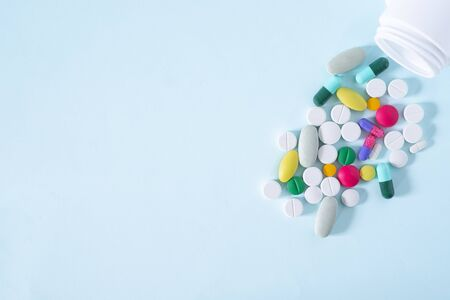 Flat Lay, Top View of Colorful, Assorted pharmaceutical medicine pills. Many pills and tablets isolated on blue background with copy space. medicine concept.