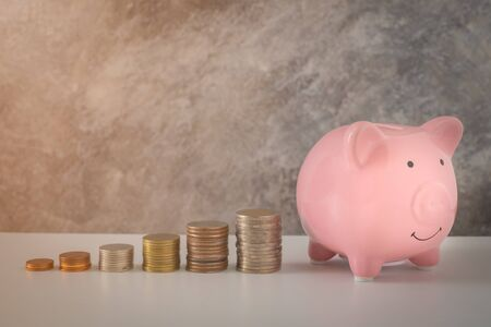 Nahaufnahme des rosa Sparschweinlächelns mit Münzstapeltreppe steigern das Wachstum, das Geld spart. Konzept Business Finance, Geld für die Zukunft sparen. mit Kopienraum.