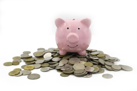 Focus of Pink piggy Bank on a pile of many coinsisolated on white background. money saving financial concept.