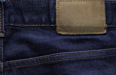 Macro, Close-up of blank leather label on new denim blue jeans trousers. fashion and retro stlye on background.