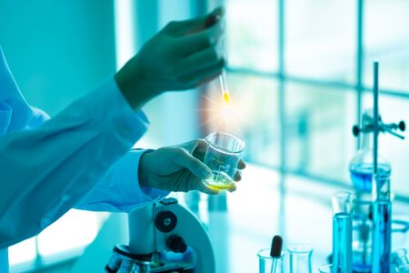 Gros plan de la main d'une femme scientifique expérimente avec un tube et un microscope. Laboratoire, il y a du matériel de verrerie différent des liquides et un ordinateur portable sur la table pour la recherche. Banque d'images