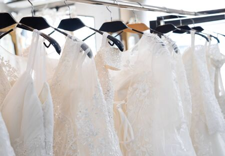 Beautiful, White bridal dress texture on background. Wedding dresses hanging on a hanger interior of bridal salon. Design, fashion modern luxury in detail.