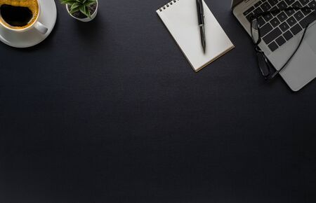 Workspace in office with black table. Top view from above of laptop with notepad and coffee. Desk for modern creative work of designer. Flat lay with blank copy space. Business and finance concept.