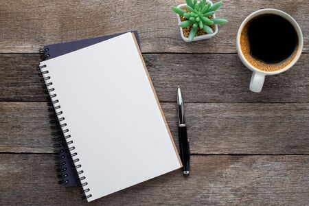Top view from above of Blank open notebook and coffee on wood table background. Workplace for the creative work of designer at home. Flat lay, Business-finance or education concept with copy space. Stockfoto