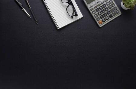 Workspace in office with black table. Top view from above of notebook with pen and glasses. Desk for modern creative work of designer. Flat lay with blank copy space. Business and finance concept. Zdjęcie Seryjne