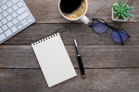 Top view from above of Blank open notebook, keyboard with glasses and coffee cup on wood table background. Workplace creative at home. Flat lay, Business-finance or education concept with copy space.