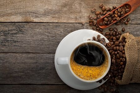 Top view above of Black hot fresh coffee with smoke and milk foam in a white ceramic cup with coffee beans roasted in burlap sack bag on wooden table background. Flat lay with copy space. Stock fotó
