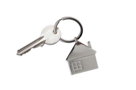 Silver key house with house shaped metal keychain on white background. Real estate concept for buying a new home.
