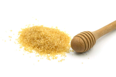 Close-up of Wooden honey dipper with Pile brown cane sugar isolated on white background.