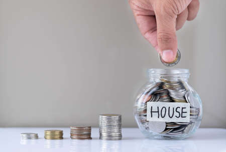 Real estate business investment and finance accounting concept. Hand putting coin into a glass bottle and house model mock-up with money step up growing growth. Saving money for buying a new house.