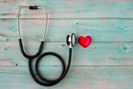 Black stethoscope with red heart of doctor for checkup on wooden table blue background. Stethoscope equipment of medical use to diagnose hear sound. Health care and cardiology concept with copy space. Stok Fotoğraf