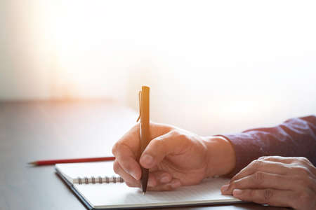 man hand using writing pen memo on notebook paper or letter, diary on table desk office. Workplace for student, writer with copy space. business working and learning education concept.