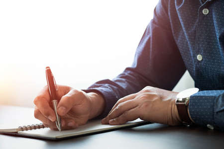 Businessman hand holding writing pen memo into notebook paper on table desk office. Workplace for business and student, writer with copy space. business working and learning education concept. Banque d'images