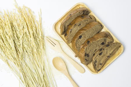 Chocolate ship sliced bread is tasty put on wooden tray near have a rice that is ingredient of bread on white background and Can be breakfast for family before going to study or work.