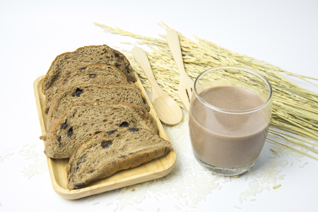 Chocolate ship sliced bread is tasty on wooden tray near have a chocolate milk and rice that is ingredient of bread on white background and Can be breakfast for family before going to study or work. Imagens