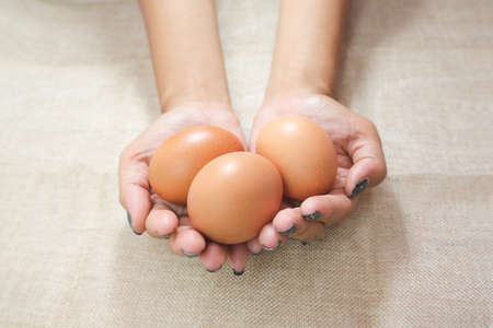 Close up of Young woman hands, holding eggs in the hands on sack background. Care or attentive concept. Selective focus.