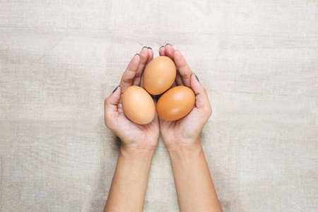 Top view of Young woman's hands, holding eggs in the hands on sack background. Selective focus. Care or attentive concept.