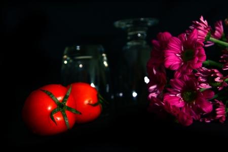 still life tomatoes , flower on black background photo
