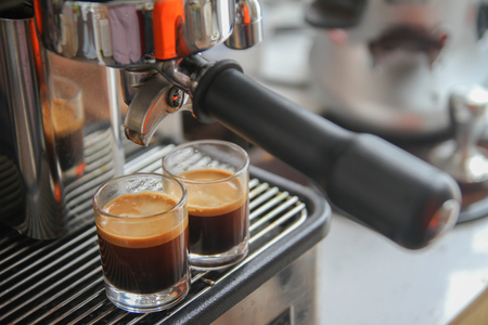Close-up of espresso machine pouring coffee in a Glass Stock Photo
