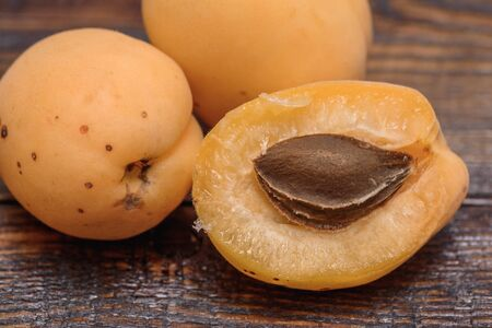 pip: half of apricot with pip on dark wooden background