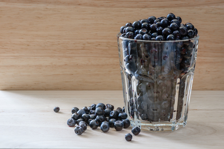 long day: Blueberries in a glass with scattered berries. Vitamin charge for long day