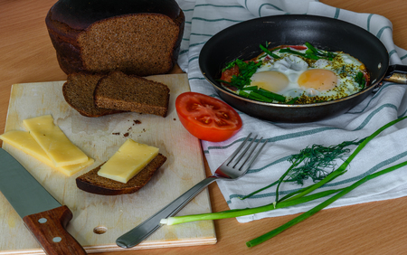 satisfying: fried eggs with herbs and tomatoes in a pan with small cheese sandwich. easy, fast and satisfying breakfast Stock Photo