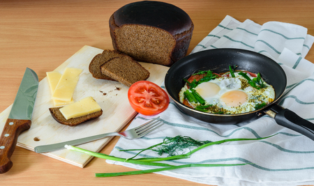 satisfying: fried eggs with herbs and tomatoes in a pan and small sandwich on board. easy, quick and satisfying breakfast