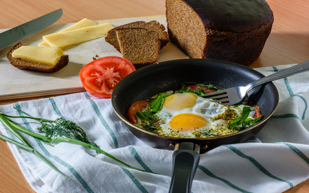 satisfying: fried eggs with herbs and tomatoes in a pan with small cheese sandwich. easy, quick and satisfying breakfast