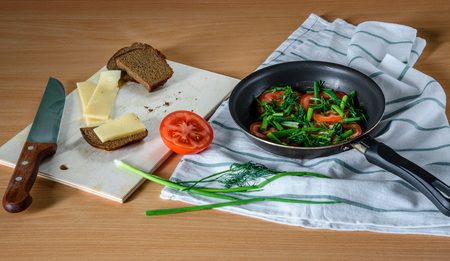 satisfying: Ingredients for fried eggs with herbs and tomatoes in a pan. easy, quick and satisfying breakfast