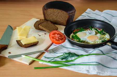 satisfying: Small sandwich on board and fried eggs with herbs and tomatoes in a pan. easy, quick and satisfying breakfast