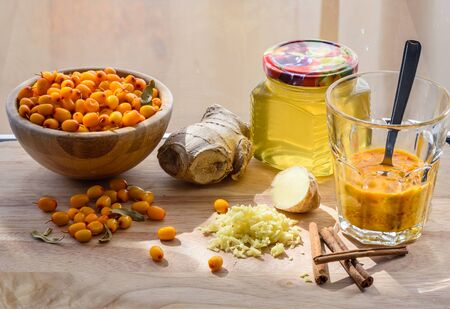 seabuckthorn: Squeezed sea-buckthorn berries in glass with other ingredients for healthy beverage. Helpful of colds Stock Photo