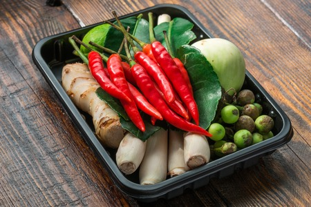 Set for Thai cooking in black plastic pallet on wooden table. Soup Tom-kha Stock Photo