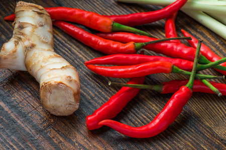 Galangal root, hot mini chili peppers with lemongrass on wooden table. Tom Kha Gai soup ingredients.