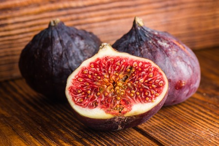 Ripe seasonal figs with half on a wooden background.